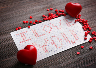 Valentine's Day concept. Beautiful gift card on wooden background, close up