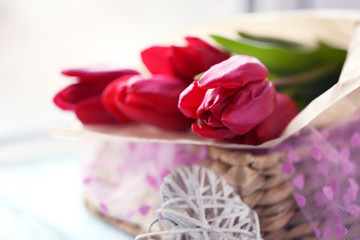 Red tulips in a wicker basket on a light-blue table