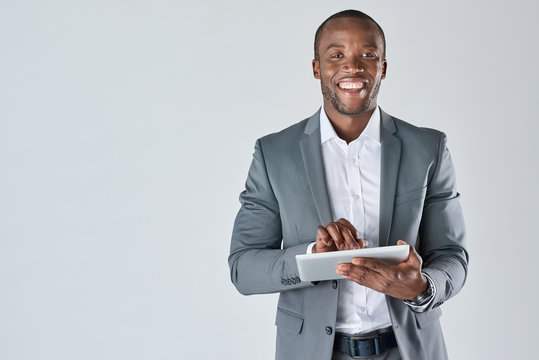 Young black male professional holding tablet device smiling