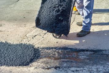 Worker empties a wheelbarrow containing asphalt during repair of a city street