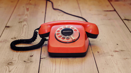 red dial phone on a wooden background