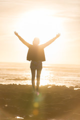 Silhouette of free woman enjoying freedom feeling happy at beach at sunset. Serene relaxing woman in pure happiness and elated enjoyment with arms raised outstretched up.
