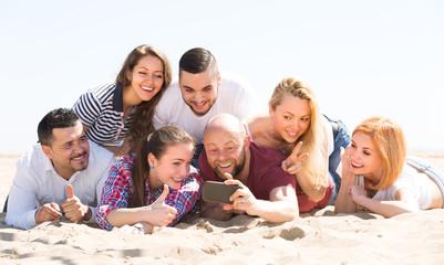 Friends making selfie at sandy beach