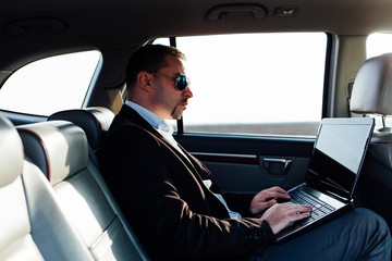 Businessman working with laptop inside the car