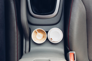 Coffee cups inside car holder between seats