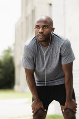 Black runner resting in city with earbuds