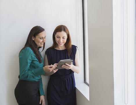 Caucasian businesswomen using digital tablet at office window