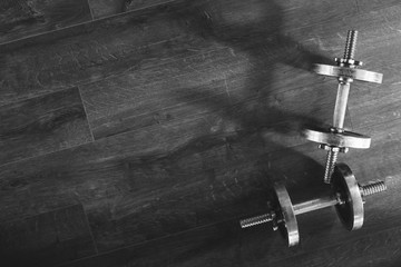 Top view of a dumbells on a wooden background in a gym, healthz