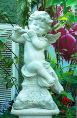 The cute statue playing flute instrument in the garden