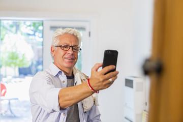 Older Hispanic artist taking cell phone photograph of art in studio