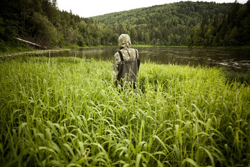 Mari man in wading boots standing in tall marsh grass