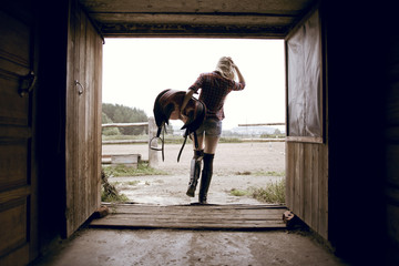 Caucasian woman carrying horse saddle in barn doorway