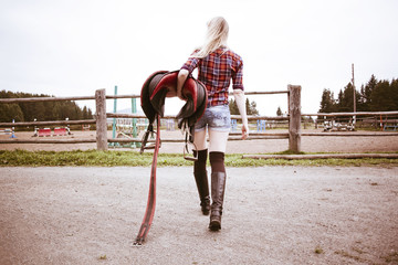 Caucasian woman carrying horse saddle on ranch