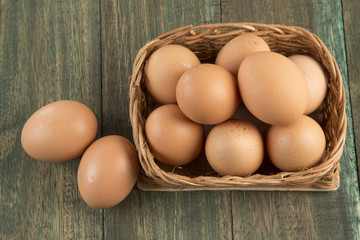 Eggs in a basket on wooden background