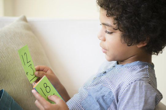 Mixed race boy using flash cards to study math