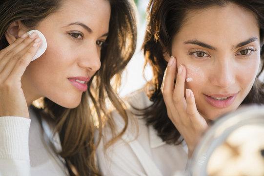 Women looking in mirror and applying facial cream