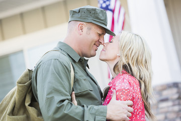 Returning Caucasian soldier hugging wife