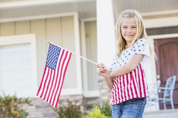 Smiling Caucasian girl waving American flag near house