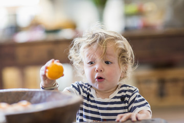 Surprised Caucasian baby boy examining fruit