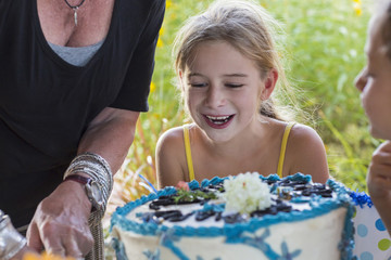 Family celebrating birthday together outdoors