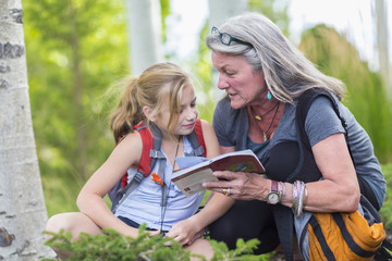 Caucasian grandmother and granddaughter reading guidebook while hiking