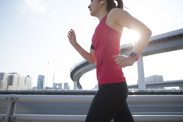 Woman runner is running the city with a wearable terminal