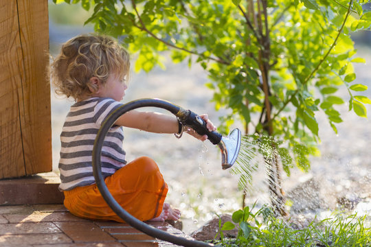 Caucasian baby boy watering plants from back patio