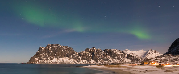 Northern lights over the sea at Utakleiv Beach, Lofoten Islands, Norway in the winter.