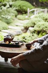 Caucasian man in robe drinking tea in zen garden