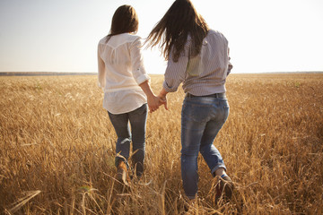 Caucasian women holding hands in rural field