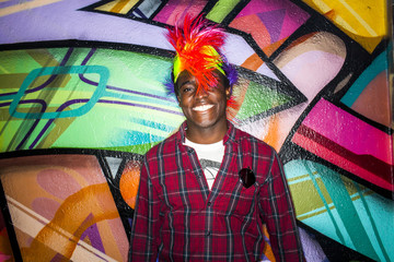 Black man in colorful wig smiling near graffiti wall