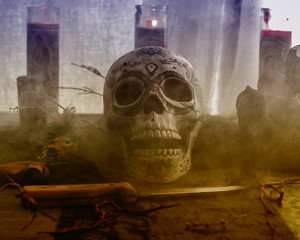 Voodoo Skull Ritual Smoke. Voodoo related objects on a table including a skull, a knife and candles. Smoke or mist.