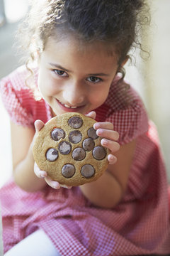 Mixed race girl eating large cookie