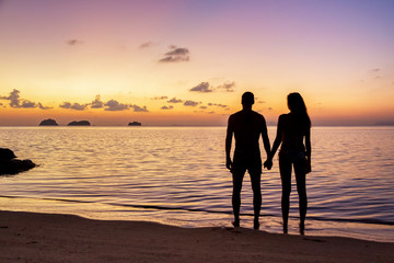 Young couple stay on the beach at sunset on Koh Samui, Thailand