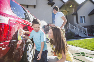 Family washing car in driveway