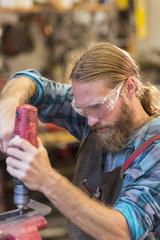 Caucasian craftsman drilling in workshop