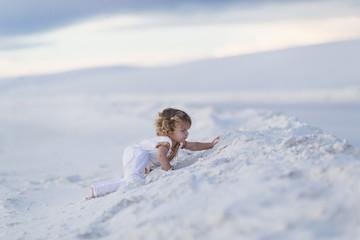Caucasian boy climbing sand dune