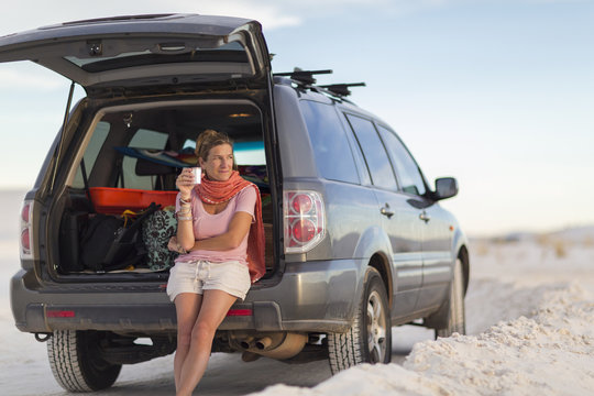 Caucasian woman leaning on car drinking coffee
