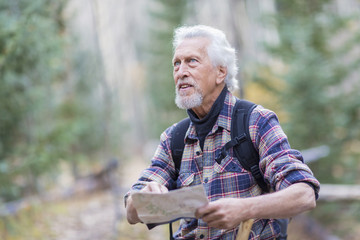 Caucasian hiker reading map in forest