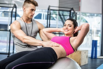 Male trainer assisting woman with sit ups