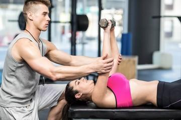Male trainer assisting woman lifting dumbbells