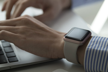 Women with a smart watch is using a laptop