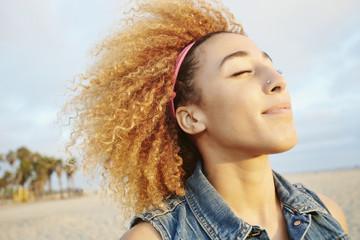 Hispanic woman smiling at beach