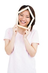 Young woman holding house shaped popsicle sticks on face