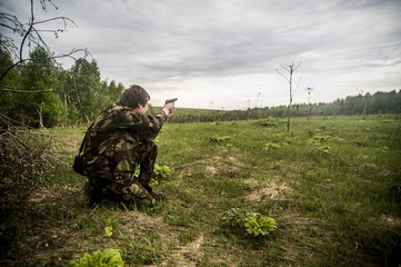 Caucasian man practicing shooting in rural field