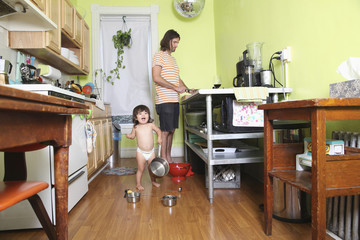 Girl playing in kitchen as father cooks