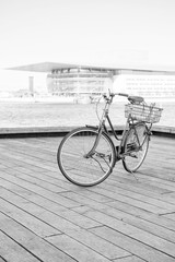 Classic vintage retro city bicycle in Copenhagen, Denmark. Opera House is on a background. Black and white photo