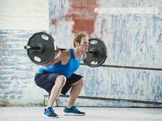Caucasian man lifting weights in warehouse