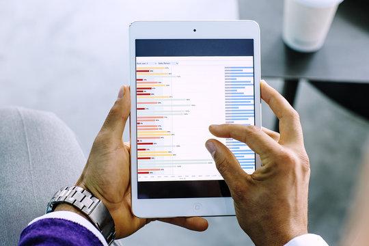 Close-up of businessman examining graph on digital tablet