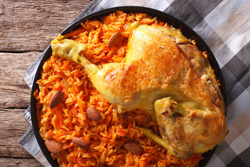 Kabsa - spicy rice with vegetables and chicken close-up. horizontal top view